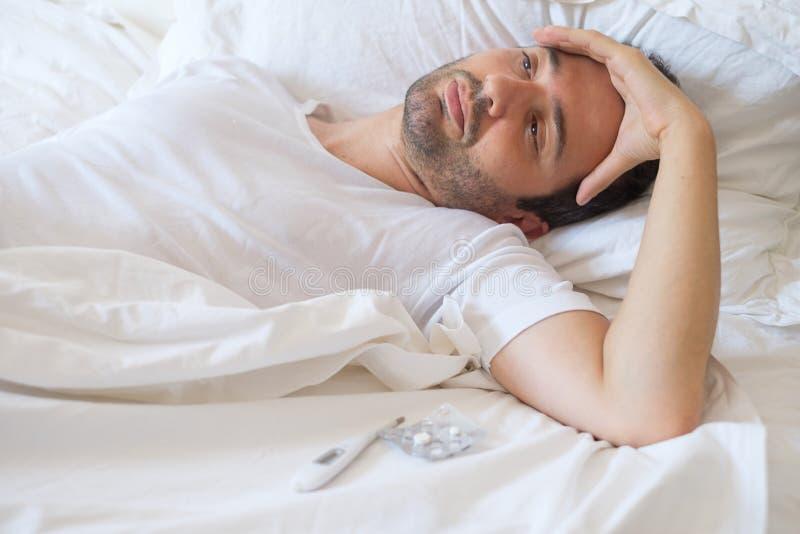 Mens die het zieke liggen in zijn bed en verward voelen voelen stock fotografie