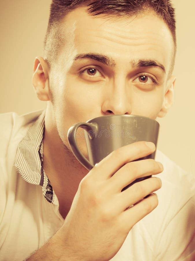 Mens die hete koffiedrank drinken cafeïne stock afbeelding