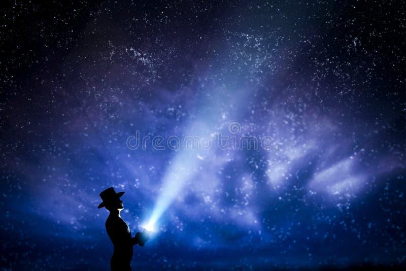 Mens die in hoed lichtstraal werpen omhoog het hoogtepunt van de nachthemel van sterren Om te onderzoeken, droom, magisch stock illustratie