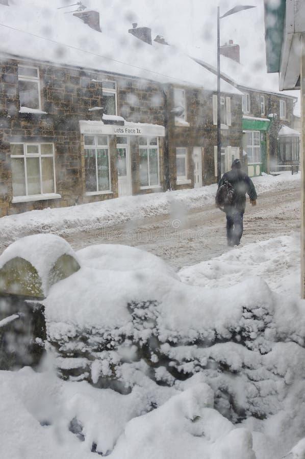Mens die hoewel zware sneeuwval langs Welse Hoofdstraat lopen stock afbeelding