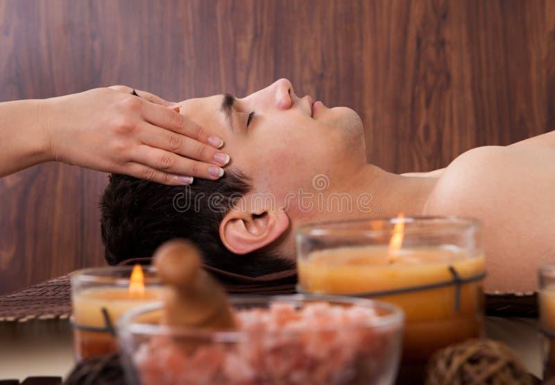 Mens die hoofdmassage van massager in kuuroord ontvangen royalty-vrije stock afbeelding