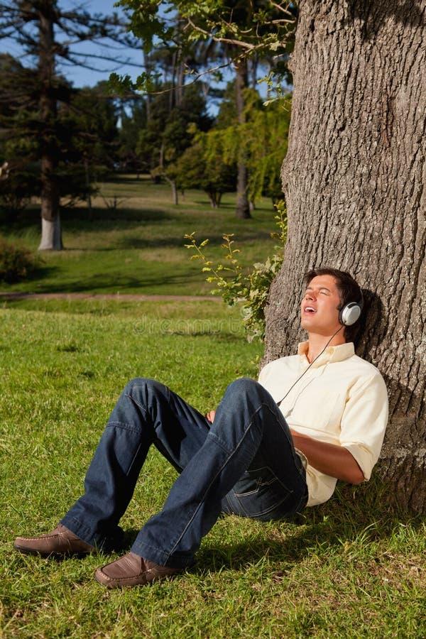 Mens die hoofdtelefoons met behulp van om aan muziek te zingen terwijl het rusten van een boom stock afbeelding