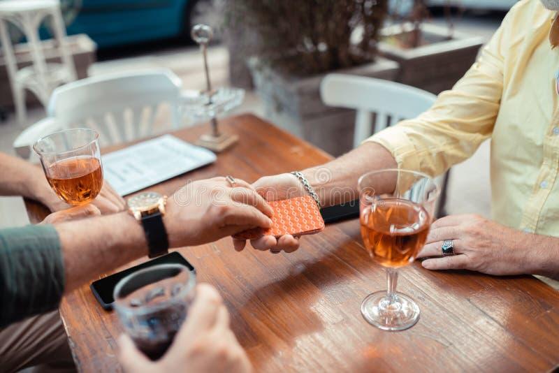 Mens die horloge dragen die kaart nemen terwijl het spelen met vrienden stock afbeelding