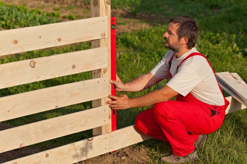 Mens die houten omheining bouwen royalty-vrije stock fotografie