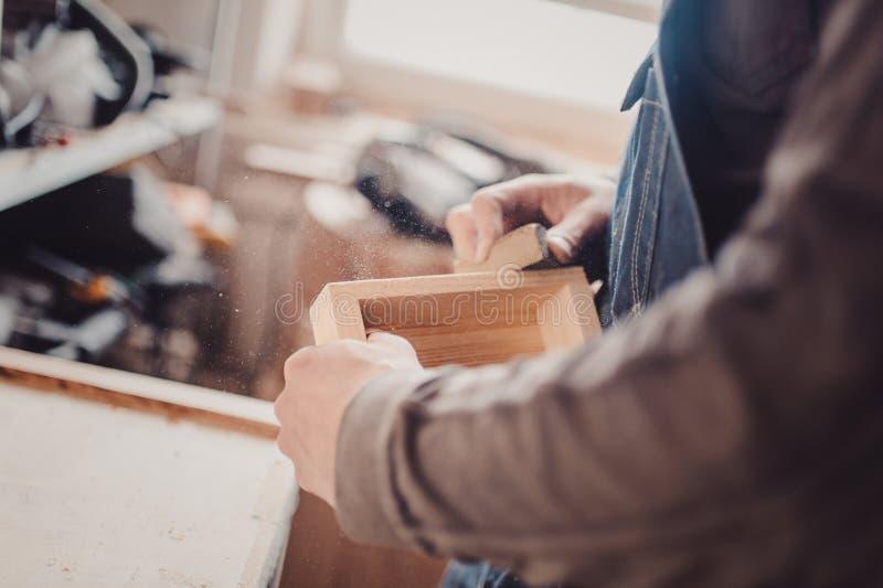 Mens die houten paneel schuren Proces van het hand schuren van een meubilairdeel stock fotografie