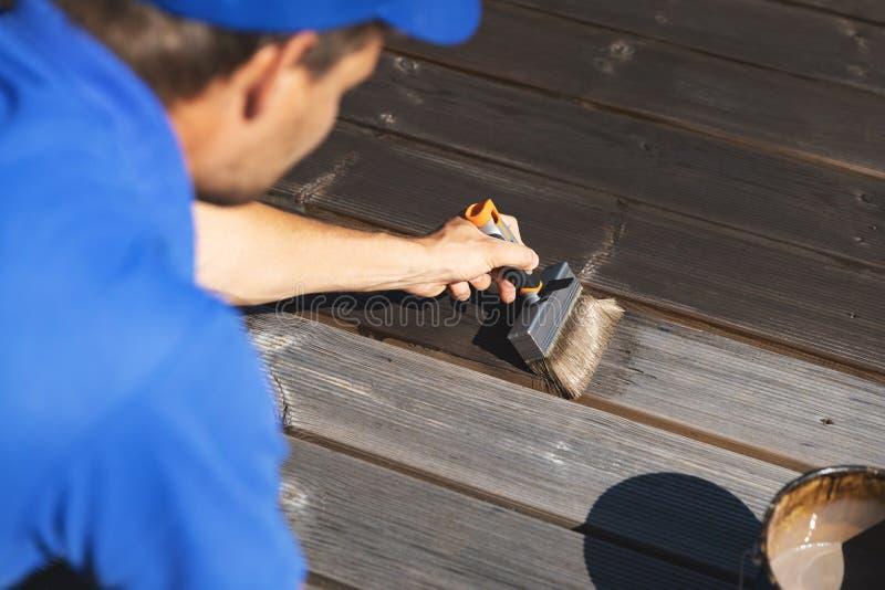 Mens die houten terrasplanken met houten beschermingsolie schilderen royalty-vrije stock afbeelding