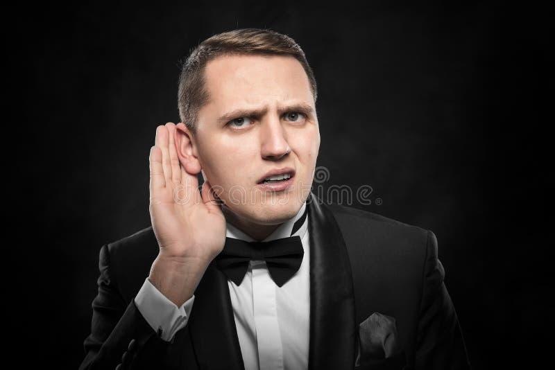 Mens die iets over donkere achtergrond luisteren royalty-vrije stock fotografie