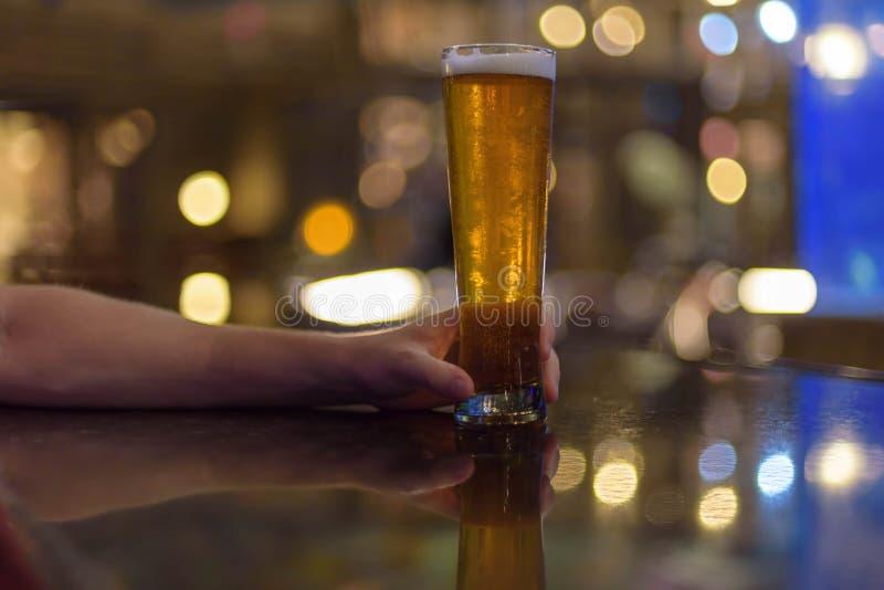 Mens die ijskoud lang bier houden bij de teller royalty-vrije stock afbeeldingen
