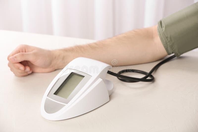 Mens die impuls en bloeddruk met sphygmomanometer controleren op lijst stock afbeeldingen
