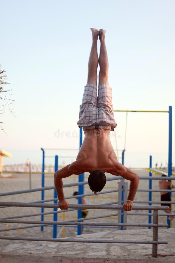 Mens die indrukwekkende sterkte tonen, die een handstand in strand doen royalty-vrije stock foto