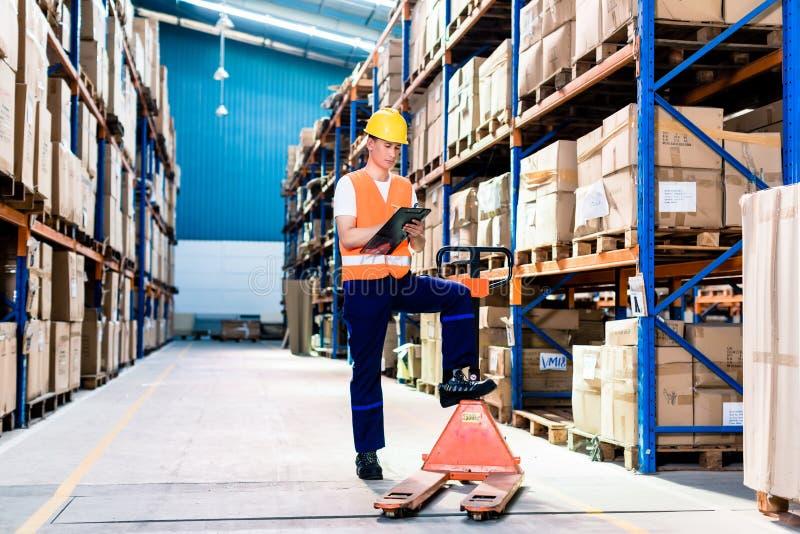 Mens die in industrieel pakhuis lijst controleren stock fotografie