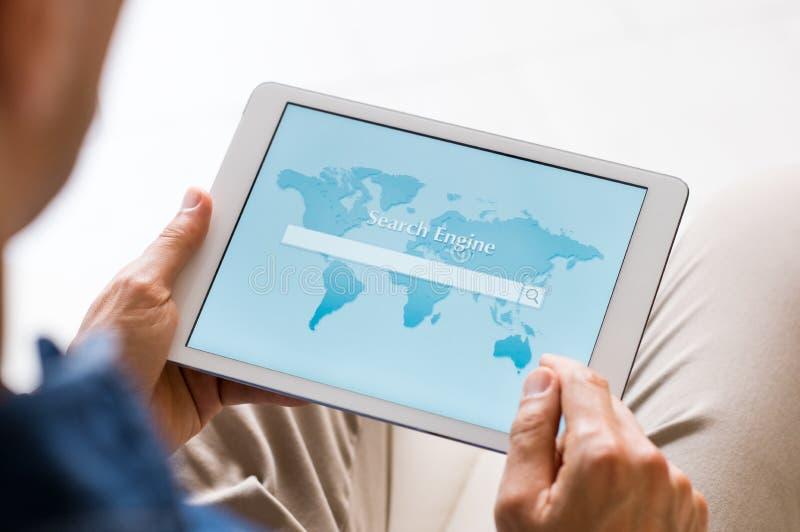 Mens die Internet-tablet gebruiken royalty-vrije stock fotografie