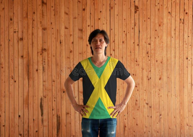 Mens die Jamaïca-het overhemd van de vlagkleur dragen en zich met met de handen in de zij op de houten muurachtergrond bevinden stock foto's