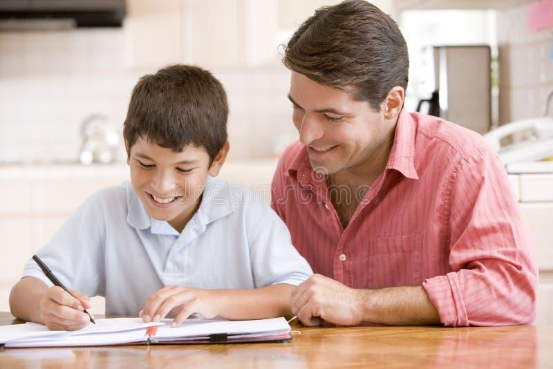Mens die jonge jongen in keuken helpt doend thuiswerk stock afbeeldingen