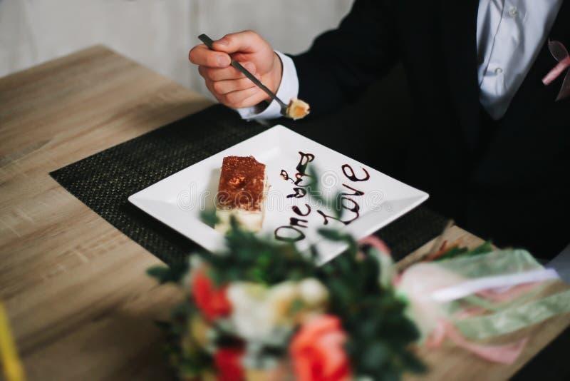 Mens die kaastaart in koffie eten Bruidegom die huwelijkscake eten royalty-vrije stock fotografie