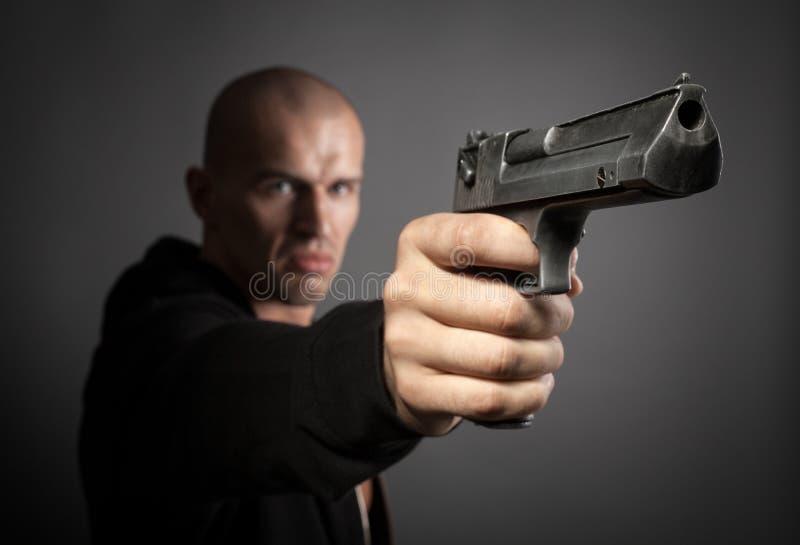 Mens die kanon op grijze achtergrond schieten stock afbeeldingen