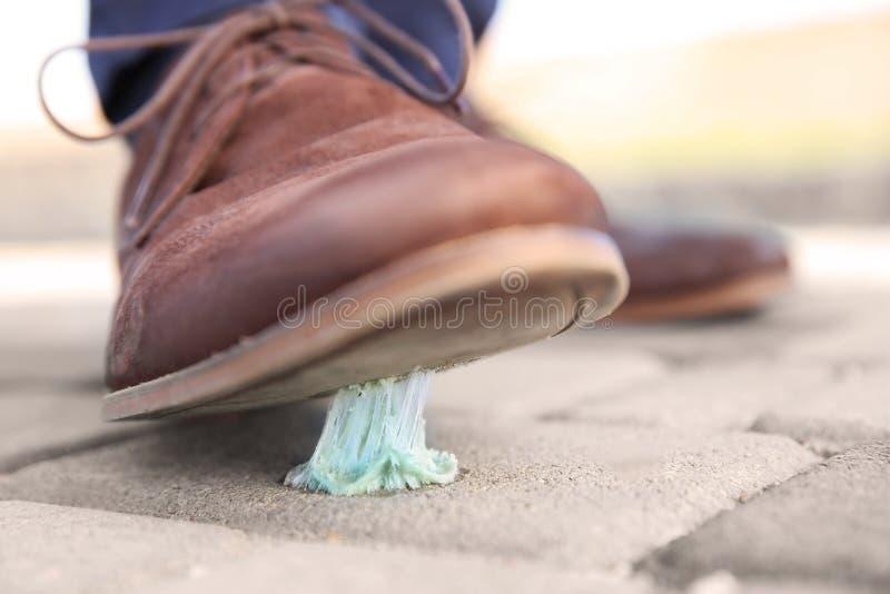 Mens die in kauwgom op stoep stappen stock fotografie