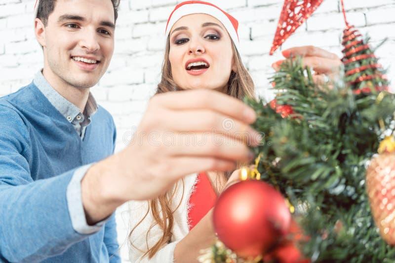 Mens die Kerstmisornament op boom zetten royalty-vrije stock afbeeldingen