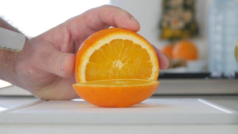 Mens die in Keuken een Fruitsalade van een Verse en Zoete Sinaasappel voorbereidt stock afbeeldingen