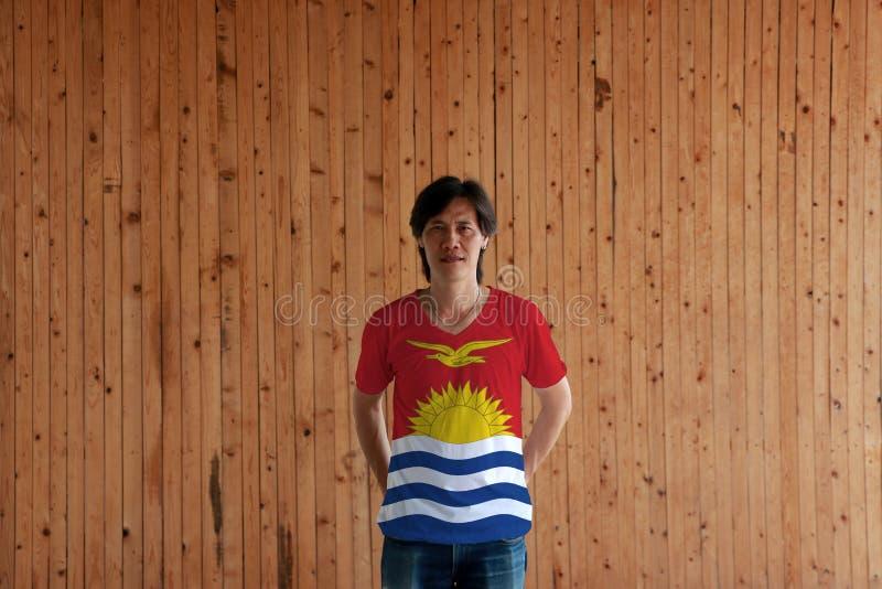 Mens die Kiribati vlagkleur van overhemd dragen en zich met gekruist achter achter de bevinden overhandigt op de houten muurachte royalty-vrije stock afbeeldingen