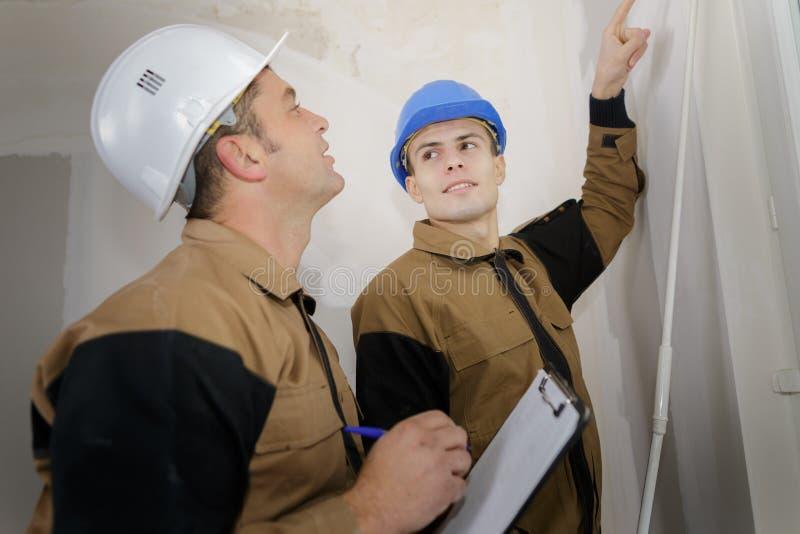 Mens die klembord bekijken terwijl de medewerker op muur richt royalty-vrije stock foto
