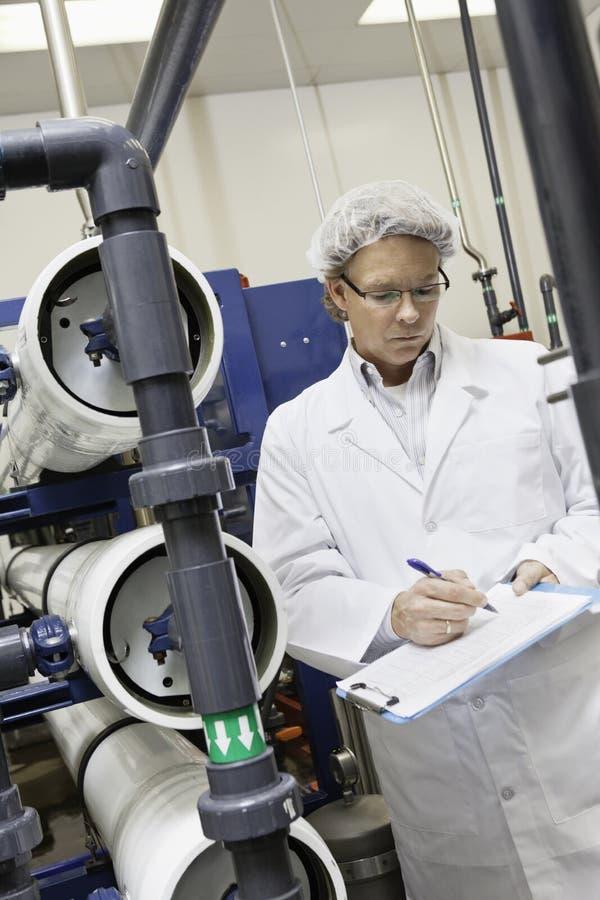 Mens die in klembord schrijven terwijl status in het bottelen van fabriek royalty-vrije stock fotografie