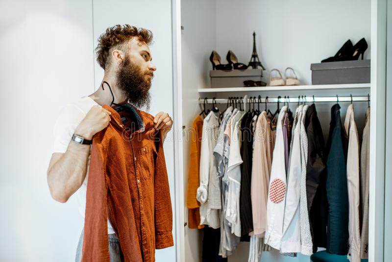 Mens die kleren in de garderobe proberen stock foto's