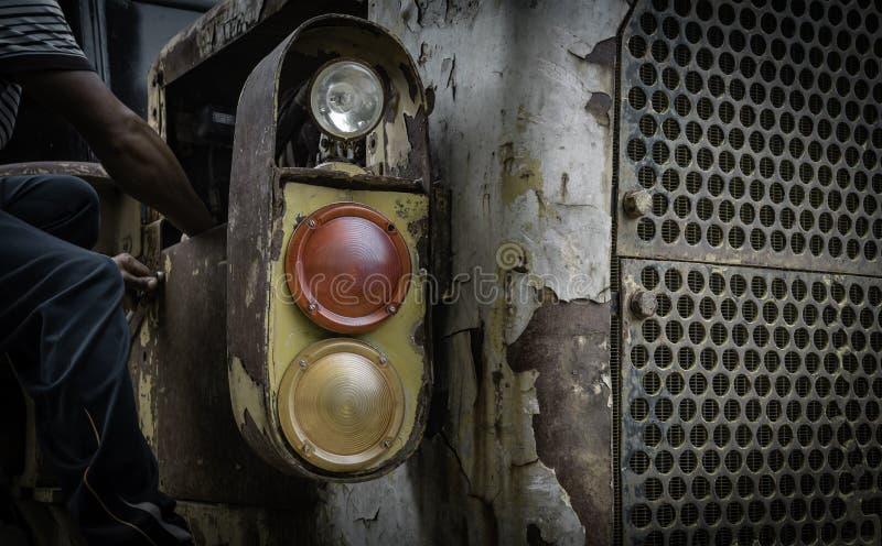 Mens die koplamp van oude tractor herstellen royalty-vrije stock afbeeldingen
