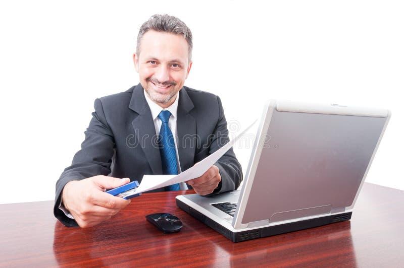 Mens die kostuum dragen bij de nietmachine en de documenten van de bureauholding royalty-vrije stock afbeeldingen