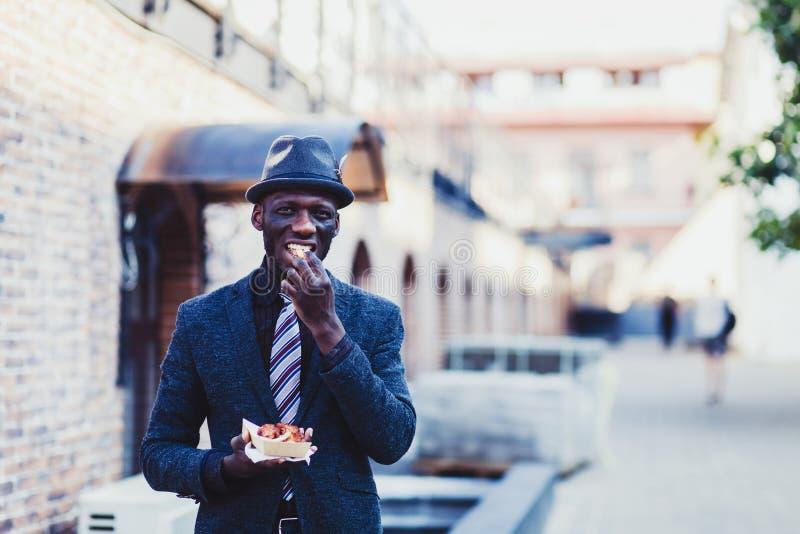 Mens die in kostuum snel voedsel eten stock fotografie