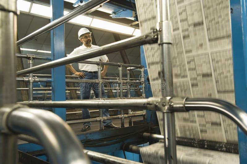 Mens die in Krantenfabriek werken stock afbeeldingen