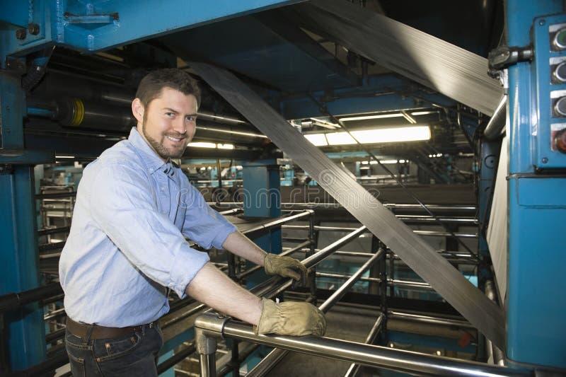 Mens die in Krantenfabriek werken royalty-vrije stock fotografie