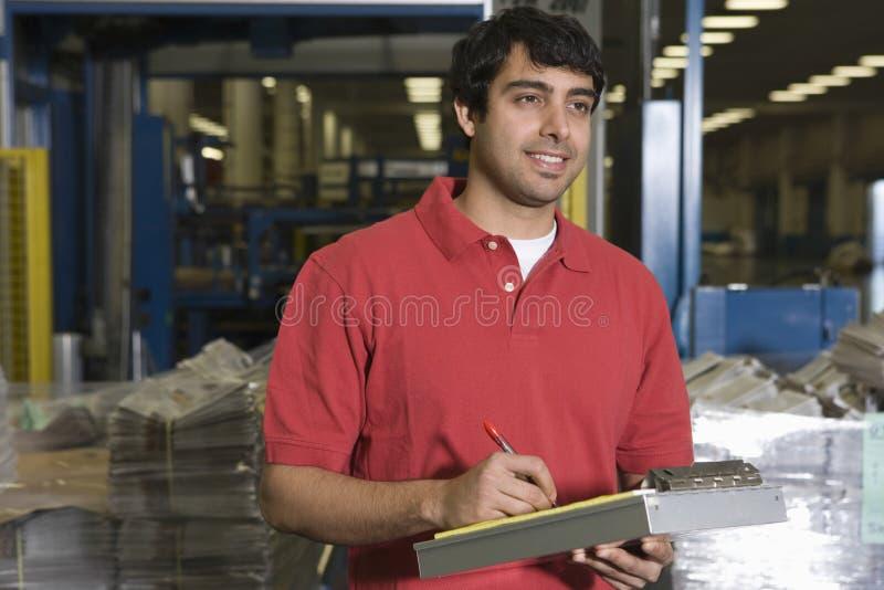 Mens die in Krantenfabriek werken stock afbeelding