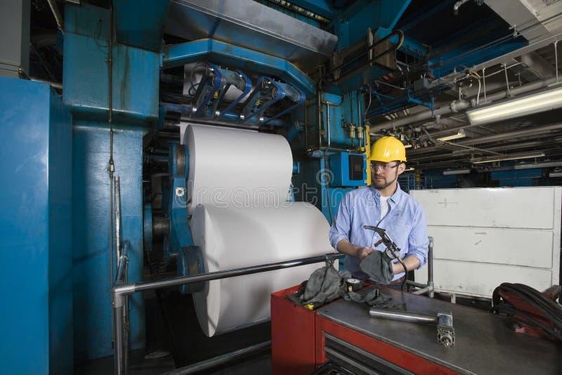Mens die in Krantenfabriek werken stock fotografie