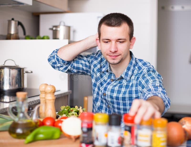 Mens die kruid toevoegen aan de salade stock afbeeldingen
