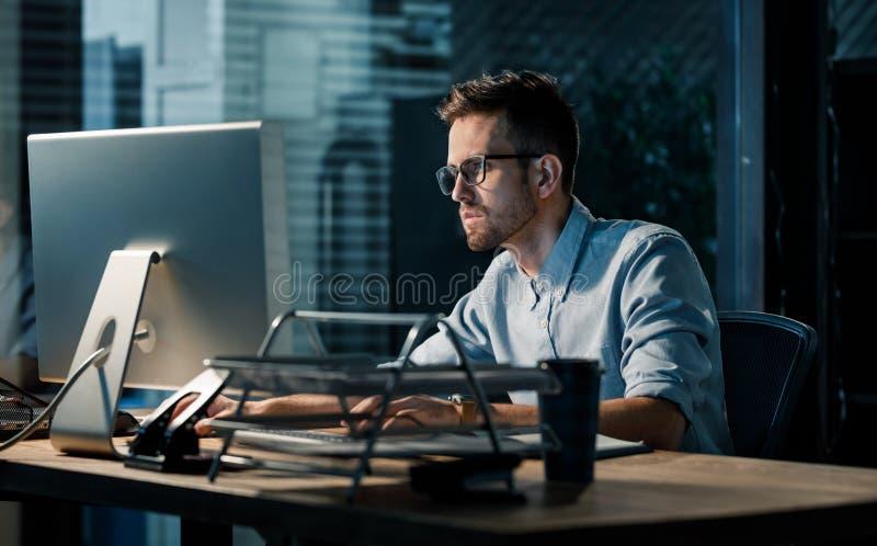 Mens die laat bij nacht in bureau werken stock foto