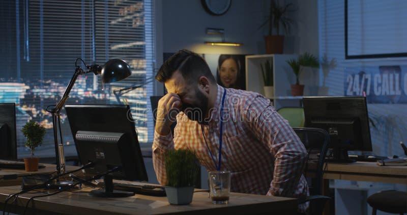 Mens die laat bij nacht in een bureau werken stock foto