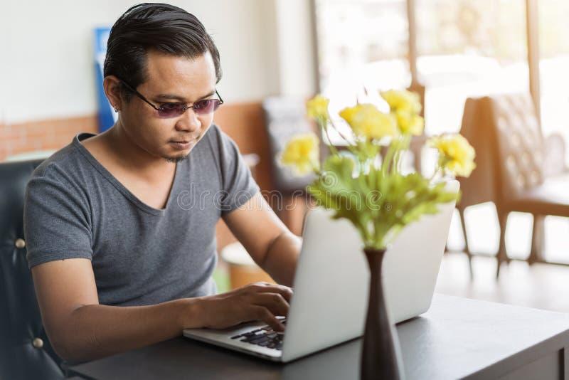 Mens die laptop computer in koffie met behulp van royalty-vrije stock foto's