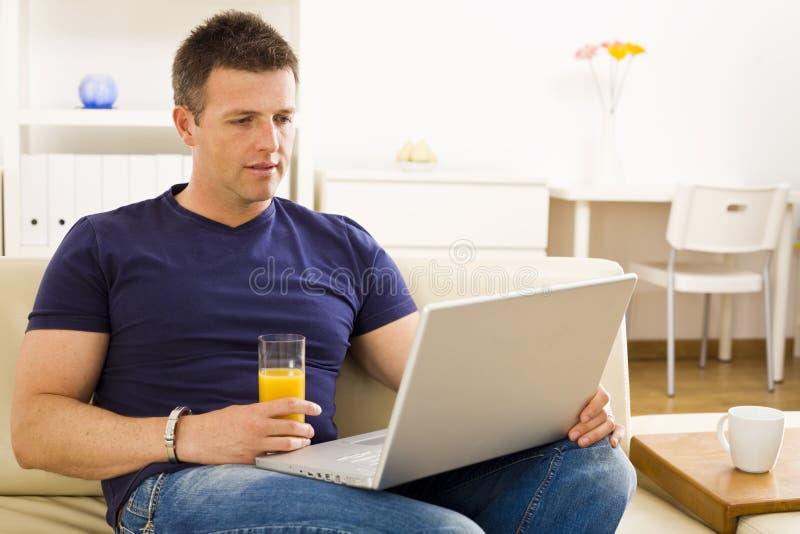 Mens die laptop computer met behulp van stock foto's