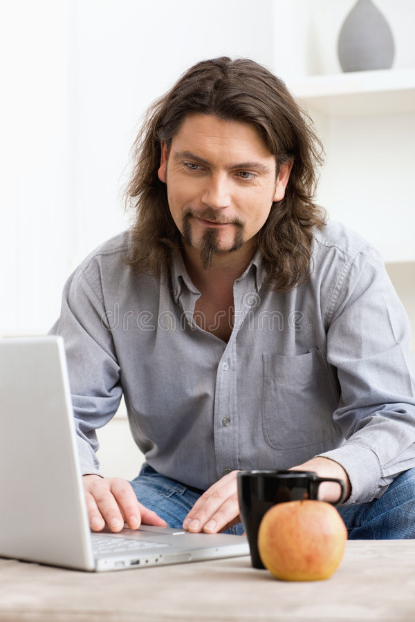Mens die laptop computer met behulp van royalty-vrije stock foto