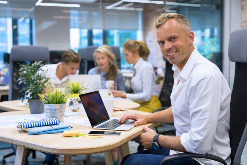 Mens die laptop in conferentieruimte met behulp van stock foto