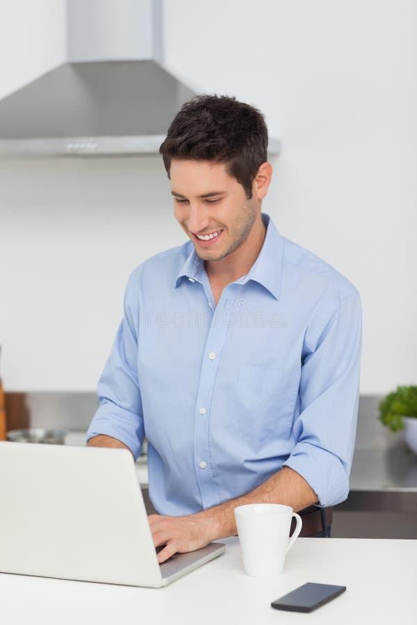 Mens die laptop in de keuken met behulp van royalty-vrije stock afbeeldingen