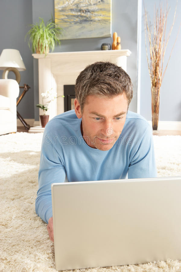 Mens die Laptop het Ontspannende thuis Leggen op Deken gebruikt stock foto's