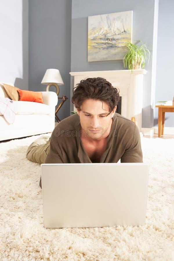 Mens die Laptop het Ontspannende thuis Leggen op Deken gebruikt royalty-vrije stock afbeelding