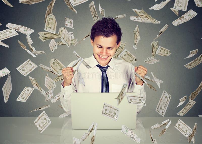Mens die laptop met behulp van die online zaken bouwen onder geldregen royalty-vrije stock foto