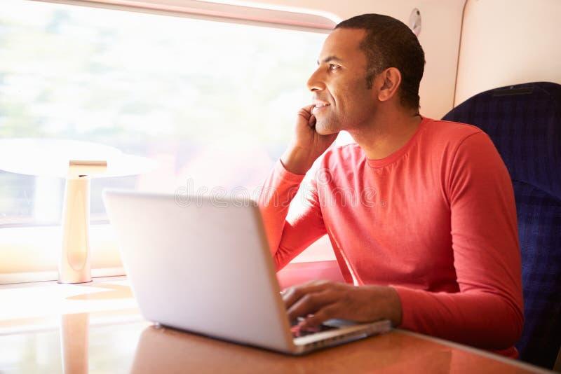 Mens die Laptop op Trein met behulp van stock foto