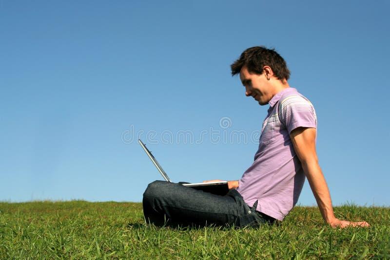 Mens die laptop in openlucht met behulp van stock foto