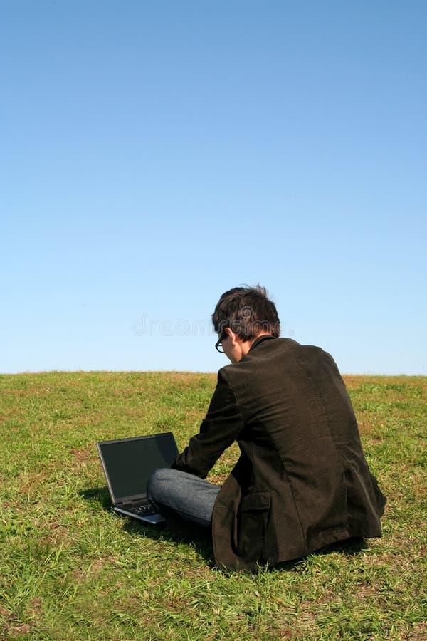 Mens die laptop in openlucht met behulp van stock afbeelding