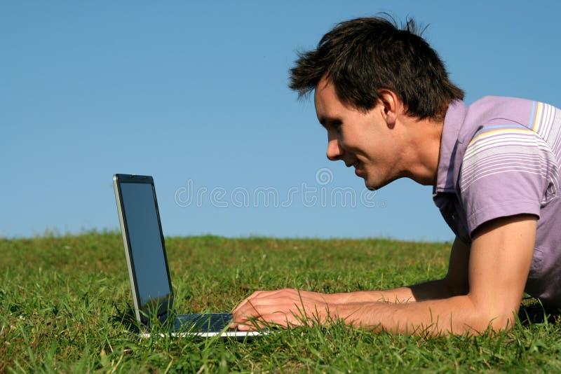 Mens die laptop in openlucht met behulp van stock afbeeldingen