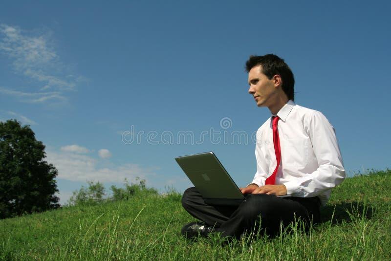 Mens die laptop in openlucht met behulp van stock fotografie